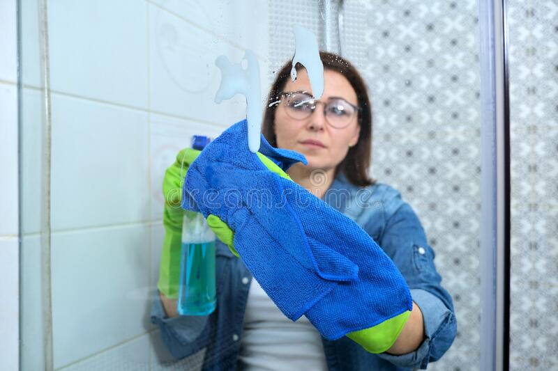 Cleaning bathroom, woman washing and polishing shower glass royalty free stock photos