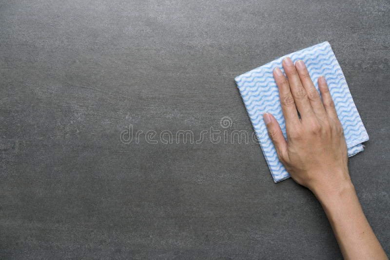 Cleaning black table by woman hand stock image