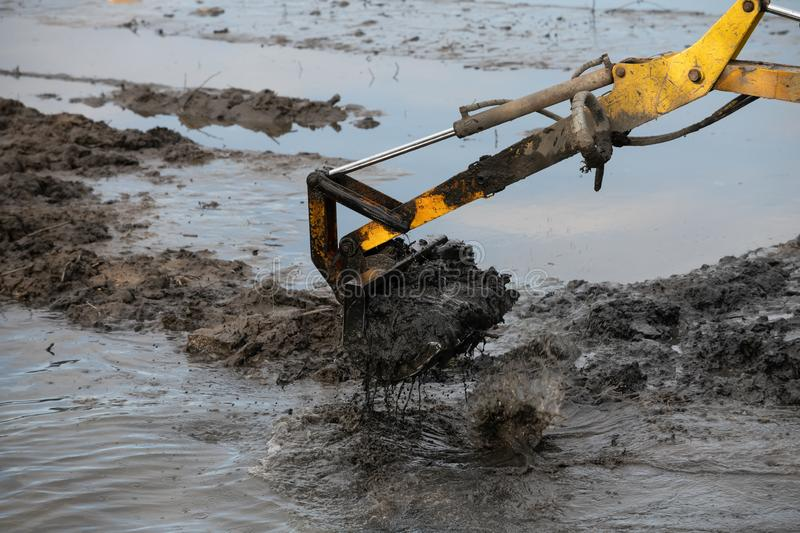 Cleaning the bottom of the lake with a dredge. Machine, pond, water, dredger, industry, machinery, mud, technology, work, ark, auger, barge, boat, boom, broach stock image
