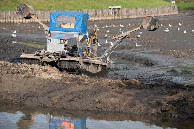 Cleaning the bottom of the lake with a dredge. Machine, pond, water, dredger, industry, machinery, mud, technology, work, ark, auger, barge, boat, boom, broach stock images