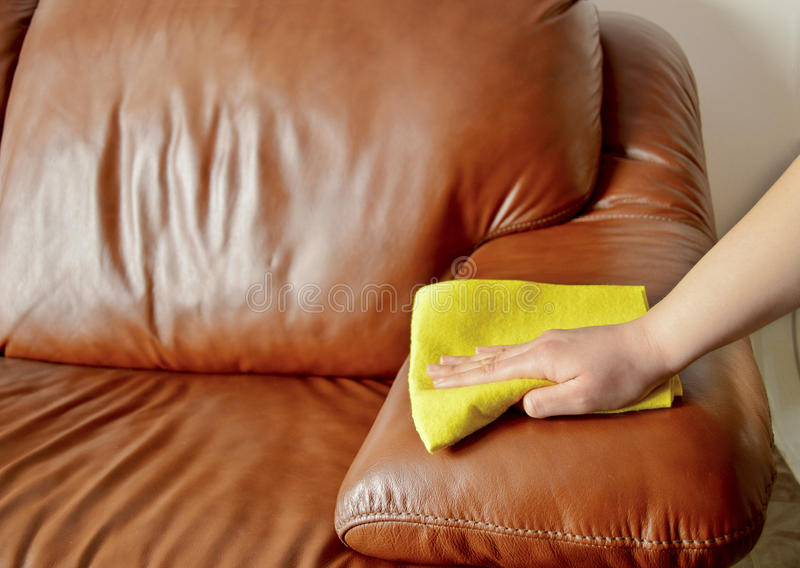 Cleaning brown sofa with a yellow cloth. Hand cleaning brown sofa with a yellow cloth royalty free stock photography