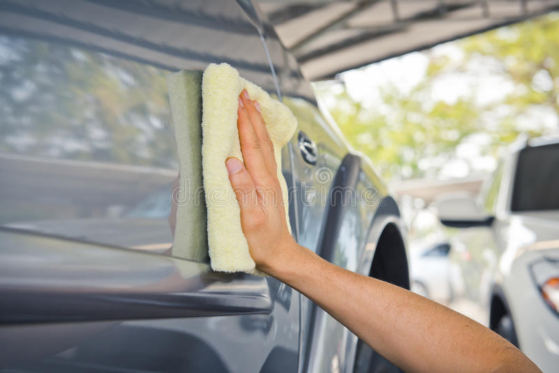 Cleaning the car with microfiber cloth and wax coating stock images