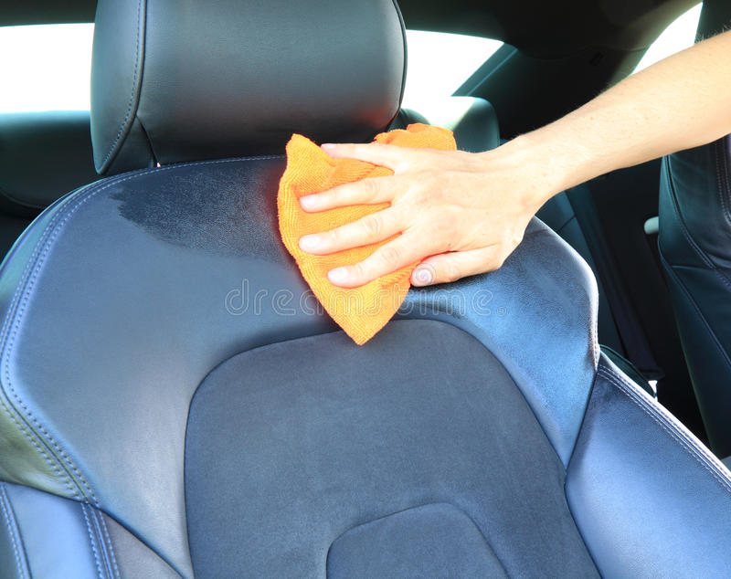 Cleaning the car seat. Man's hand cleans a leather car seat stock photography