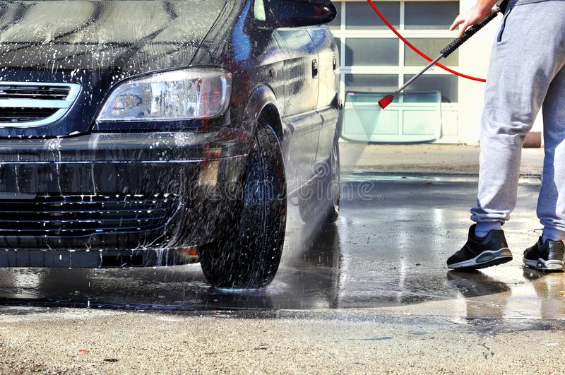 Cleaning Car Using High Pressure Water. Man washing car under high pressure water in service stock images