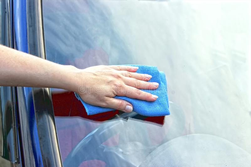 Cleaning the car using water. The man washing his car, in the palm of the fabric, close-up stock photography
