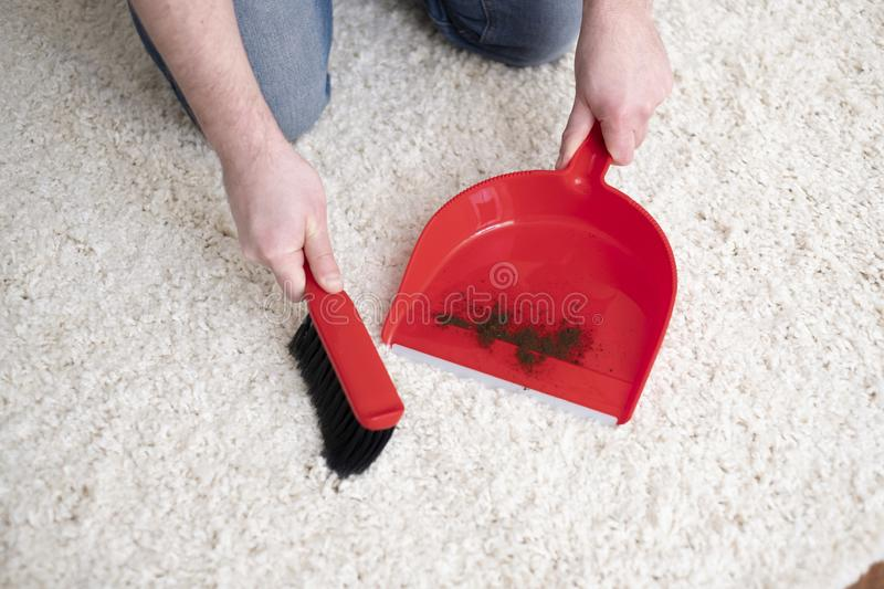 Swiping white carpet from dirty using broom. Cleaning carpet with small broom and red dustpan royalty free stock images