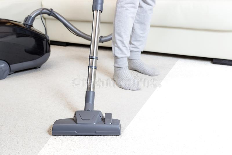 Cleaning the carpet with vacuum cleaner in the living room. Light coloured royalty free stock image