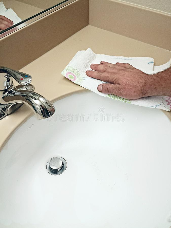 Cleaning Cleaning a bathroom sink. This is me cleaning a bathroom sink at home to make sure it's clear of bacteria and gross germs royalty free stock image