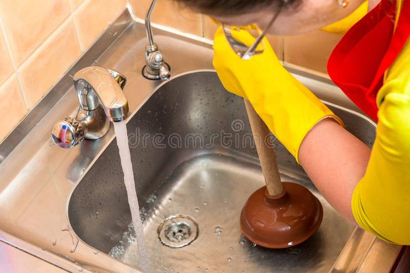cleaning clogged pipes in the kitchen sink stock image