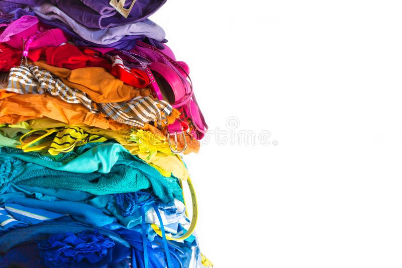 A stack of colored things on a chair. Cluttering of clothes. Cleaning in the closet. Clothes stacked in a bunch of flowers. Women`s wardrobe. Many things royalty free stock photo
