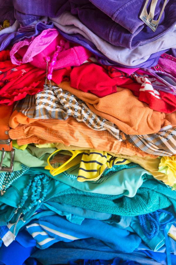 A stack of colored things on a chair. Cluttering of clothes. Cleaning in the closet. Clothes stacked in a bunch of flowers. Women`s wardrobe. Many things royalty free stock photos