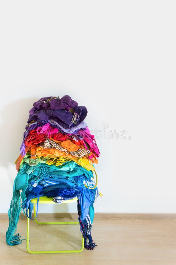 A stack of colored things on a chair. Cluttering of clothes. Cleaning in the closet. Clothes stacked in a bunch of flowers. Women`s wardrobe. Many things stock photos