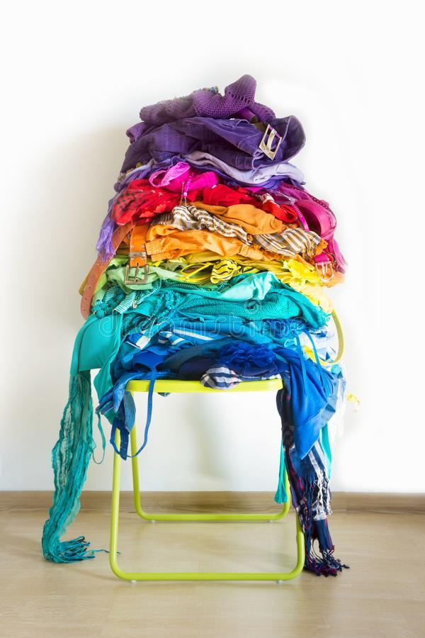 A stack of colored things on a chair. Cluttering of clothes. Cleaning in the closet. Clothes stacked in a bunch of flowers. Women`s wardrobe. Many things stock image
