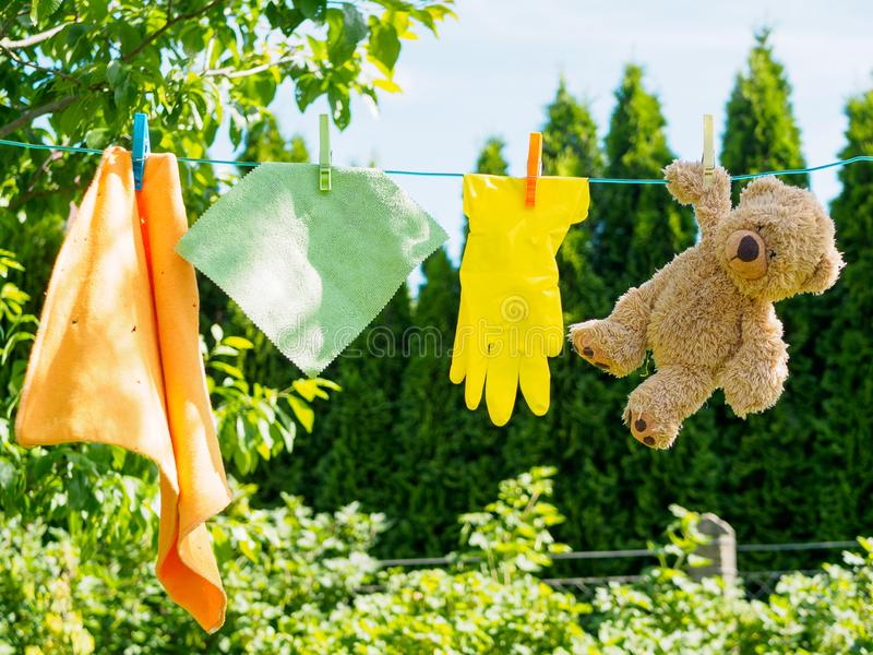 Cleaning cloths and teddy bear on a clothesline. Colorful cleaning cloths, yellow rubber glove and a brown Teddy bear on a clothesline in the garden, trees royalty free stock photos