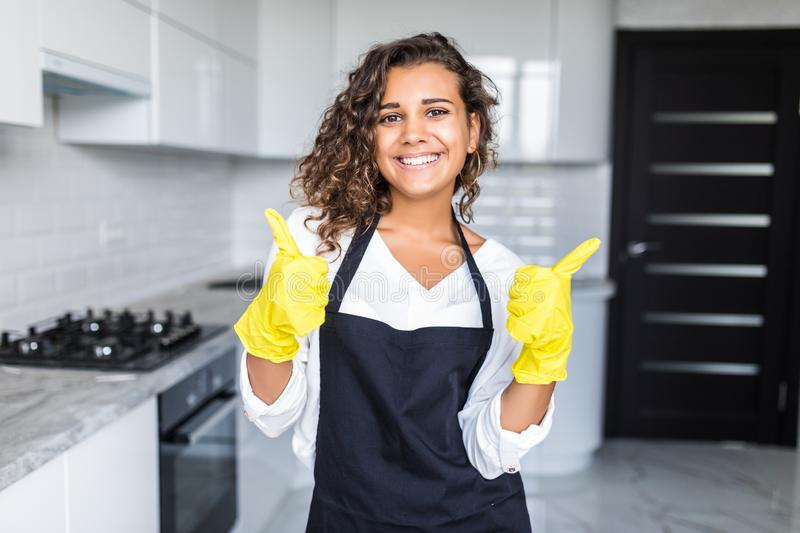 Cleaning company concept. Portrait of beautiful positive young woman - employee of cleaning company in rubber gloves with rag royalty free stock photography