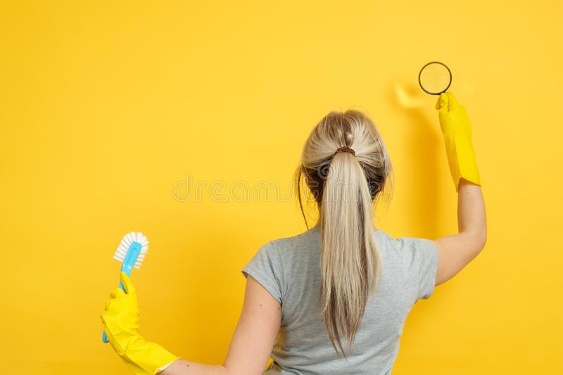 Cleaning company home office cleanup magnifier. Cleaning company. Professional home office cleanup. Woman in rubber gloves with magnifier and brush on yellow stock photo