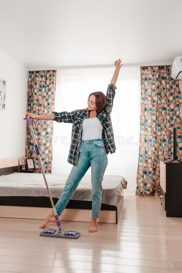 Cleaning concept. Beautiful young brunette woman doing cleaning, dancing with a mop. Room on the background. Vertical orientation.  royalty free stock image