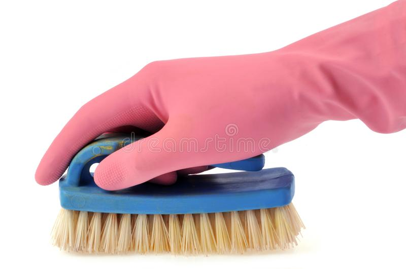 Gloved hand holding a brush in closeup on white background royalty free stock image