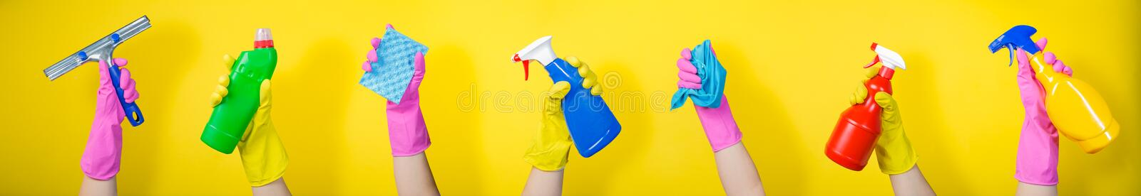 Cleaning concept - hands holding supplies on bright background royalty free stock photo