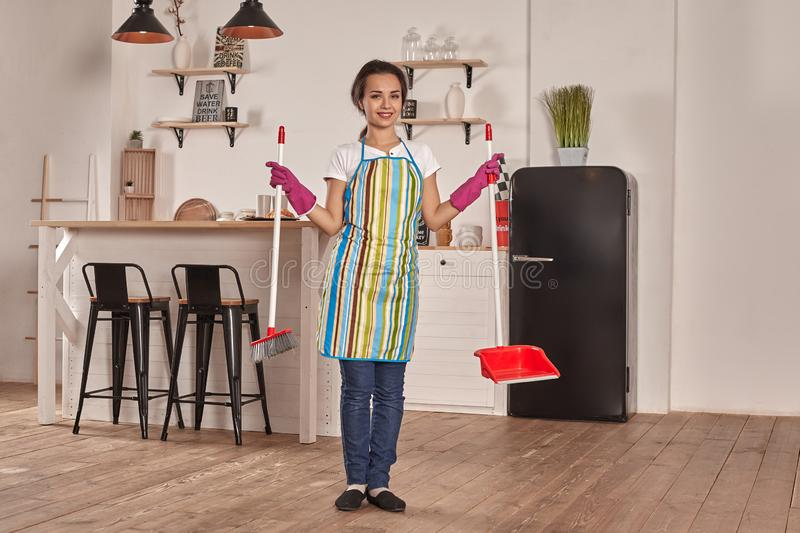 Young woman sweeping floor on the kitchen stock photography