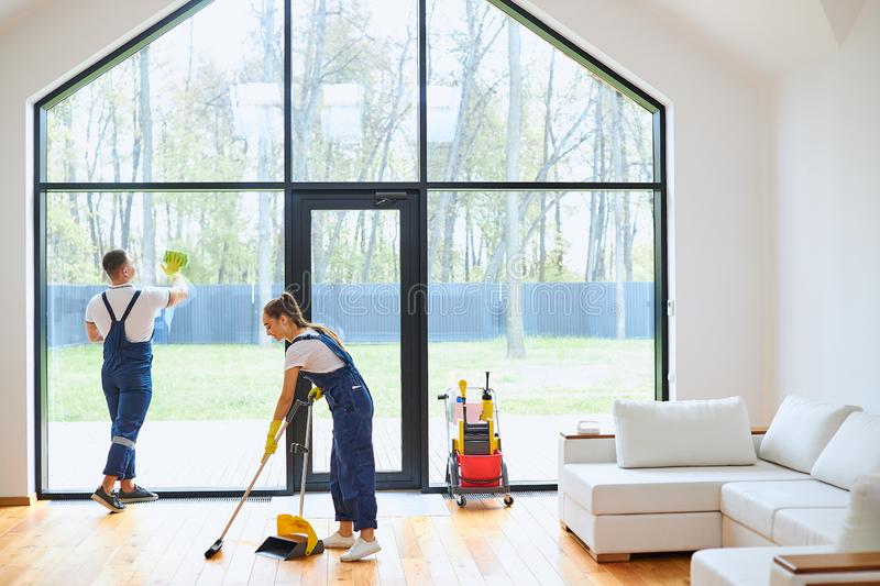 Cleaning concept. Young woman washing floor, while man cleaning window royalty free stock photography