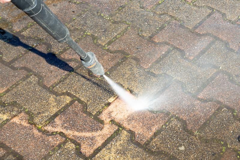 Cleaning concrete block floor by high pressure water jet outdoor. A Cleaning concrete block floor by high pressure water jet outdoor stock photo