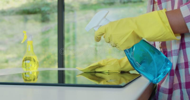 Cleaning cooktop cooking panel in kitchen with fat remover spray and a duster by a woman in yellow rubber gloves. Cleaning cooktop cooking panel in kitchen with royalty free stock photo