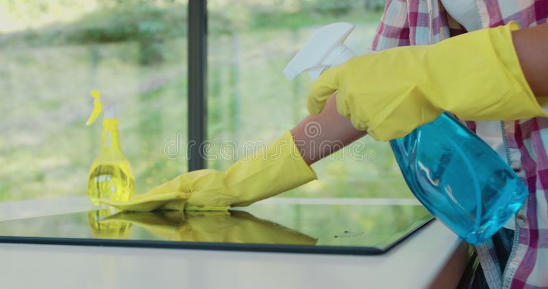 Cleaning cooktop cooking panel in kitchen with fat remover spray and a duster by a woman in yellow rubber gloves. Cleaning cooktop cooking panel in kitchen with stock photography