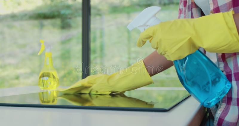Cleaning cooktop cooking panel in kitchen with fat remover spray and a duster by a woman in yellow rubber gloves. Cleaning cooktop cooking panel in kitchen with royalty free stock image