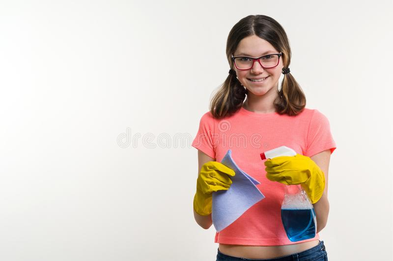 Cleaning day, spring cleanup, housework concept. Girl teenager in yellow gloves with rag and spray detergent. royalty free stock photos