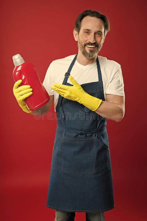 Cleaning day today. Bearded guy cleaning home. Cleanliness and order. Cleaning service and household duty. So dirty. Man. In apron with gloves hold plastic stock image