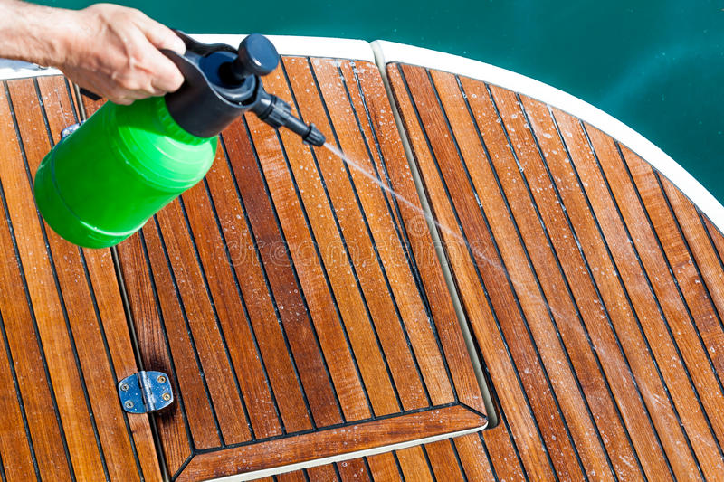 Cleaning Deck. Spraying cleaning solution on deck of boat royalty free stock photography