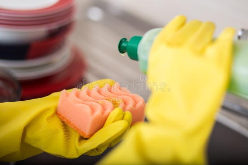 Cleaning dishware kuchennego zlew gąbki domycia naczynie Zakończenie up kobiet ręki w żółty ochronny gumowy rękawiczek myć zdjęcie royalty free