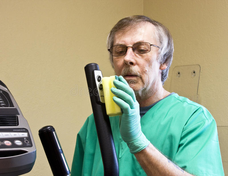 Cleaning equipment. Housekeeping worker cleaning and disinfecting some exercise equipment stock image