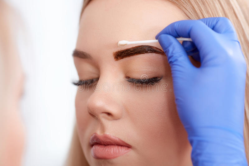 Cleaning face of client during permanent make up. stock images