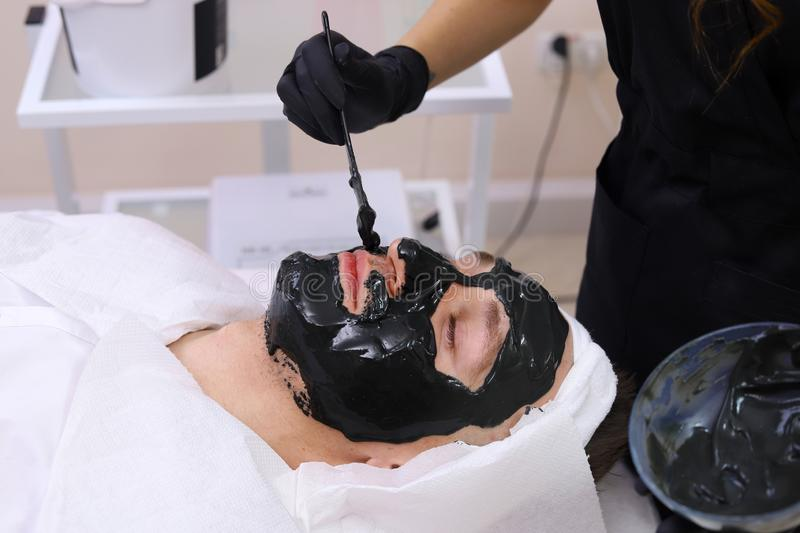 Spa therapy for men receiving facial black mask. Cleaning the face of a men in a beauty salon. Spa therapy for men receiving facial black mask royalty free stock photo