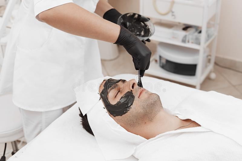 Spa therapy for men receiving facial black mask. Cleaning the face of a men in a beauty salon. Spa therapy for men receiving facial black mask royalty free stock photography