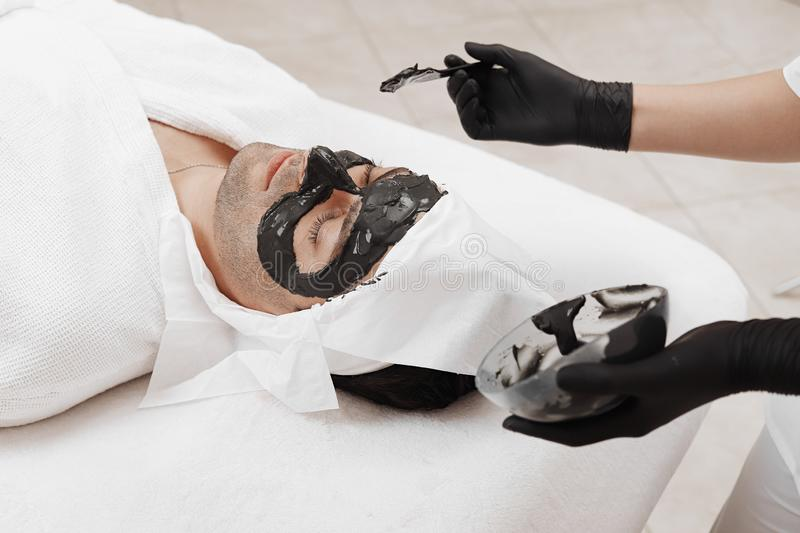 Spa therapy for men receiving facial black mask. Cleaning the face of a men in a beauty salon. Spa therapy for men receiving facial black mask stock images