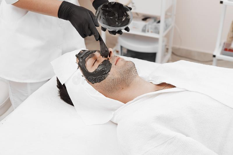 Spa therapy for men receiving facial black mask. Cleaning the face of a men in a beauty salon. Spa therapy for men receiving facial black mask royalty free stock images