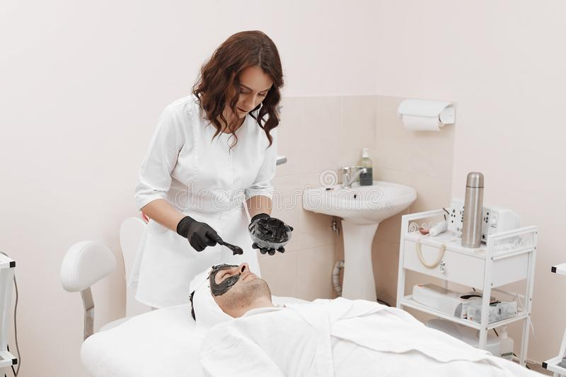 Spa therapy for men receiving facial black mask. Cleaning the face of a men in a beauty salon. Spa therapy for men receiving facial black mask stock image