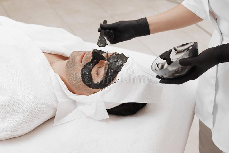 Spa therapy for men receiving facial black mask. Cleaning the face of a men in a beauty salon. Spa therapy for men receiving facial black mask stock photography
