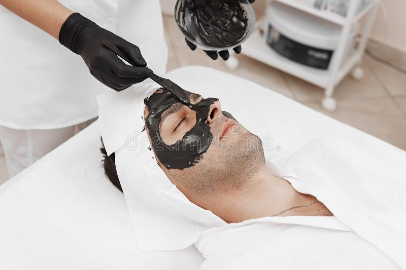 Spa therapy for men receiving facial black mask. Cleaning the face of a men in a beauty salon. Spa therapy for men receiving facial black mask stock photos