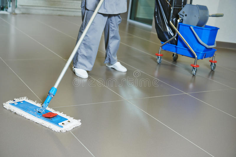 Cleaning floor. Cleaner with mop and uniform cleaning hall floor of public business building