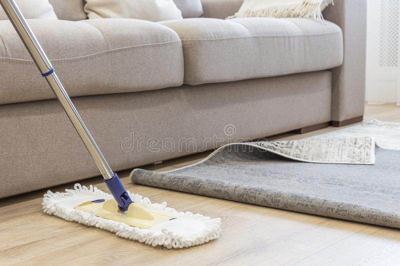 Cleaning floor with mop under carpet in living room stock photography