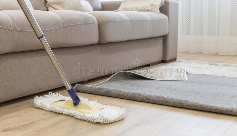 Cleaning floor with mop under carpet in living room royalty free stock image