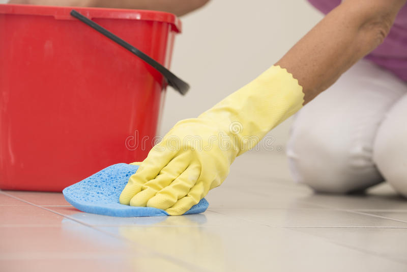 Cleaning floor tiles with glove and sponge. Close up Hand in yellow rubber glove cleaning floor tiles with sponge, with woman, housewife in blurred background royalty free stock images