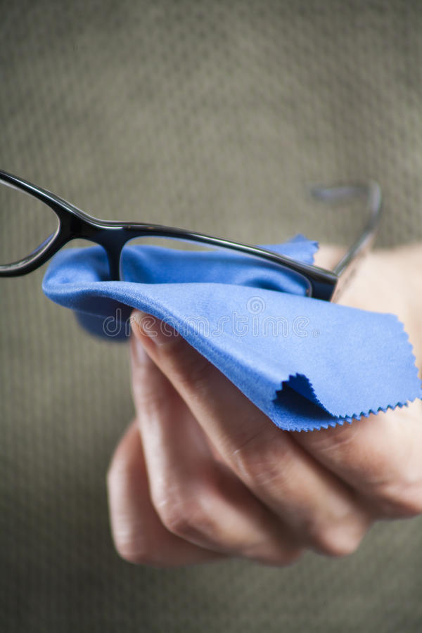 Cleaning glasses with blue cloth royalty free stock photo