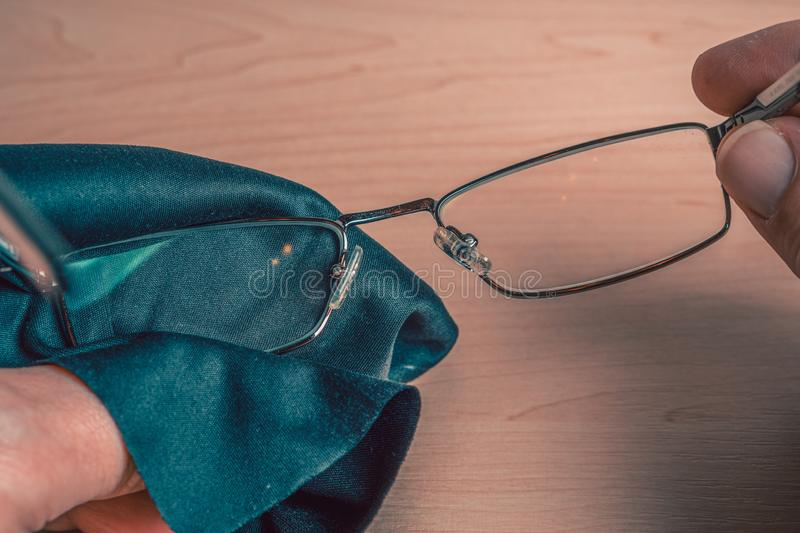 Cleaning glasses. A man wipes his glasses with a cloth. Storage and care for glasses. Selective focus stock image