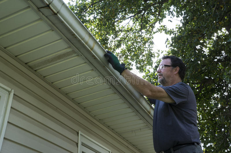 Cleaning Gutters Of Leaves And Sticks stock photo