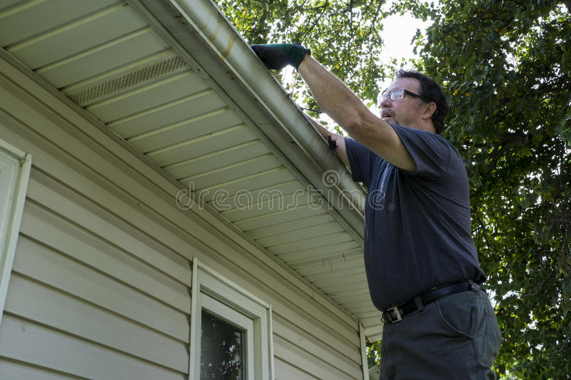 Cleaning Gutters On A Residential Home stock image